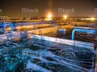 Modern wastewater treatment plant of chemical factory at night. Water purification tanks.